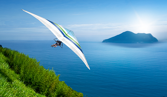 Hang glider flying over land and sea
